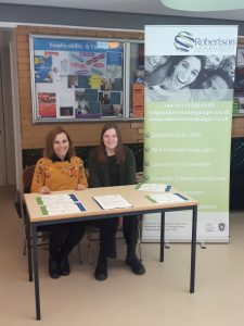 Lucia and Chloe sitting at the desk at Surrey University Career Fair