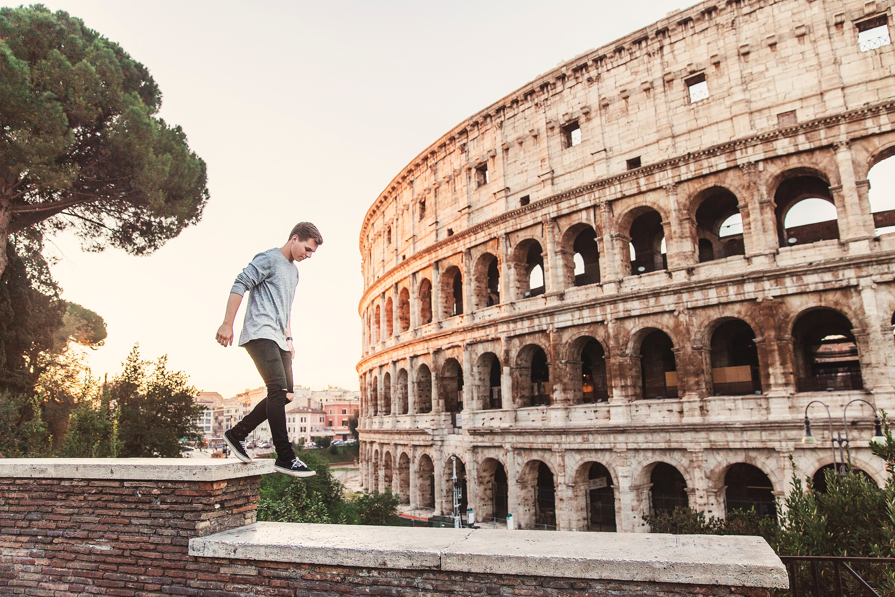 A picture of a man, walking next to the Colosseum, Italy