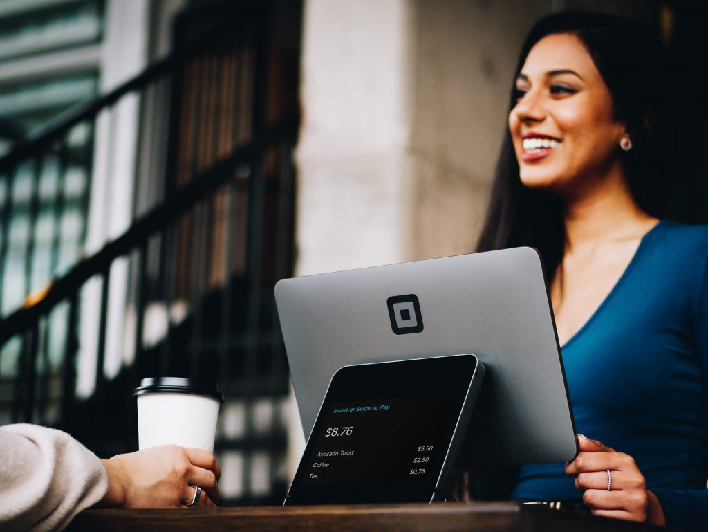 An employee smiles at her laptop. Managing remote teams well can boost well-being for all your employees.