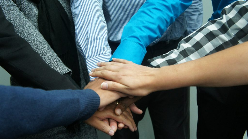 Co-workers clasp hands in a circle, symbolising the strength of their remote team culture